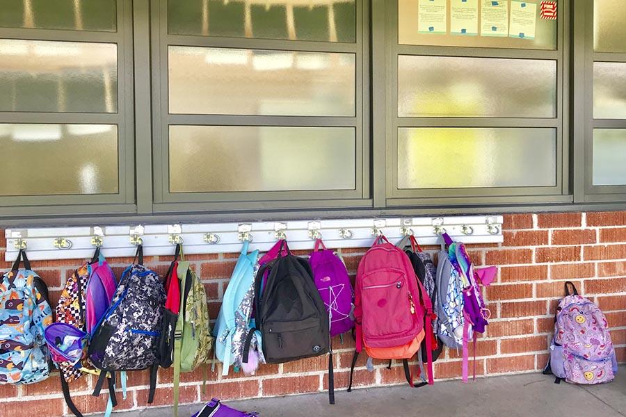 教室の外に並ぶバックパック。 たくさんの色や形が並ぶ【写真:小田島勢子】