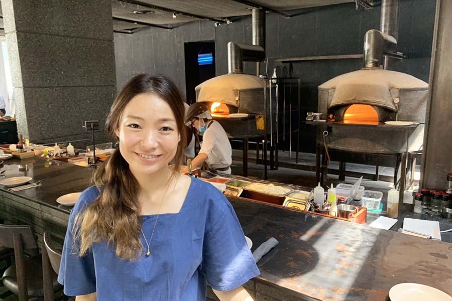 PIZZA 4PSコーポレーションのCOO高杉早苗さん。背後には店自慢のピザ窯が【写真:Hint-Pot編集部】