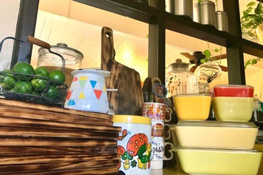 木やホーロー、陶器など素材にこだわったお気に入りの食器が並ぶ棚【写真:小田島勢子】