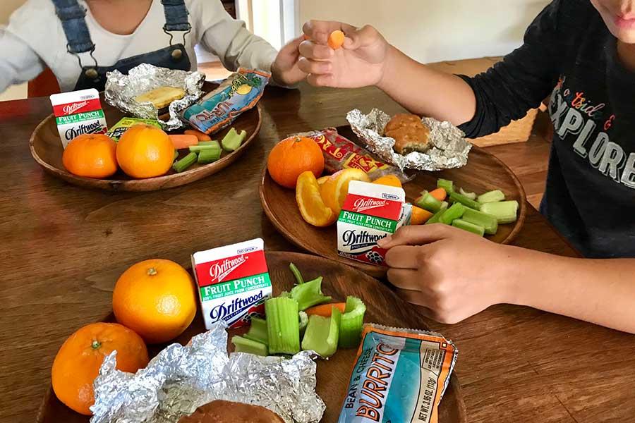 学校で無料配布された給食を食べる娘たち。栄養バランスを考えフルーツなどをプラス【写真:小田島勢子】
