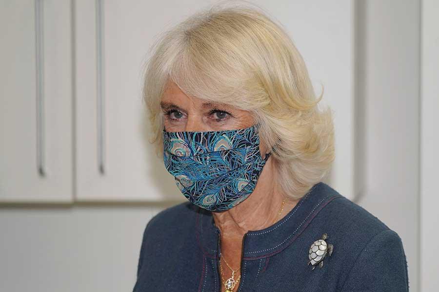 マスク姿のカミラ夫人。クジャクの羽根模様が印象的【写真:AP】