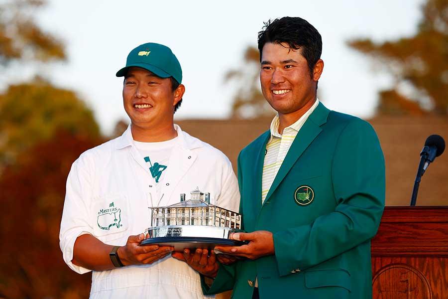 トロフィーを手に笑顔の松山英樹選手(右)と、キャディの早藤将太さん【写真:Getty Images】